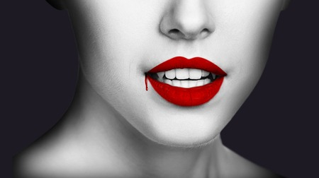 Sexy vampire woman lips with dripping blood. Closeup of  girl vampire mouth