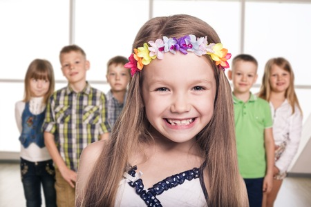 Group of smiling kids standing together and cute girl foreground