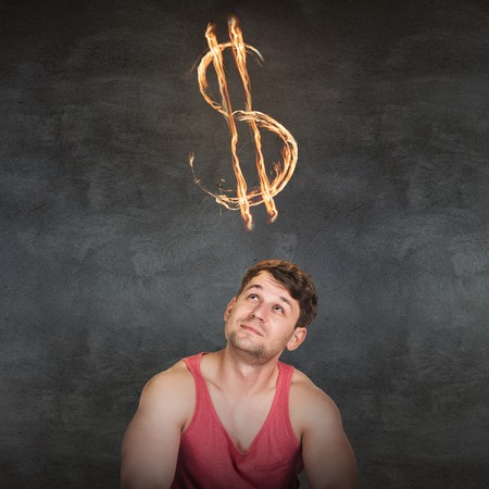 overhead: Man and currency symbol overhead blazing on the gray background Stock Photo