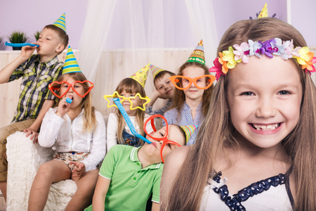 boy sitting: Happy smiling children celebrating birthday party at home