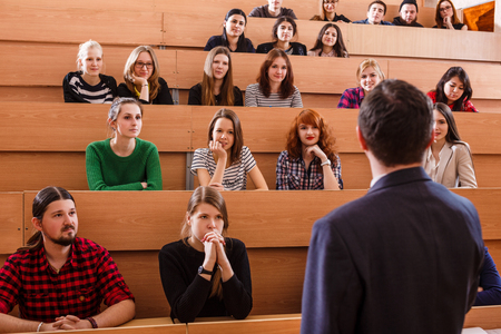 narrate: Teacher explaining something to students in classroom Stock Photo