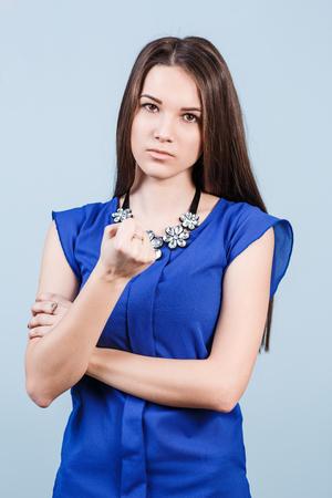 threaten: Strict beautiful woman shows threaten fist on the blue background