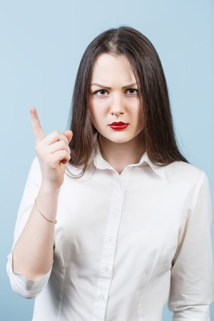 threaten: Young angry woman threaten finger on the blue background