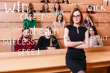 lecture hall: Teacher with crossed hands and students in classroom Stock Photo