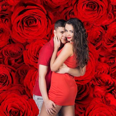 femme brune sexy: Beau couple embrasse et serrant sur le fond rouge roses Banque d'images