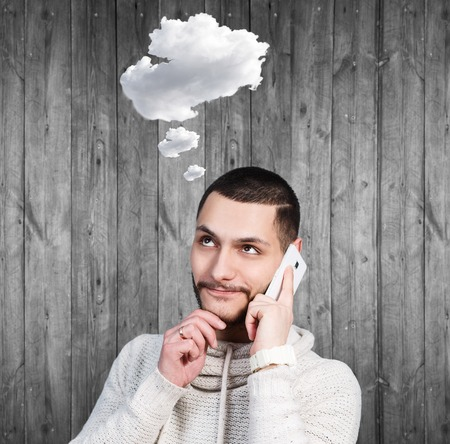 daydream: Young man daydream and speak on the phone with cloud owerhead on the wooden background