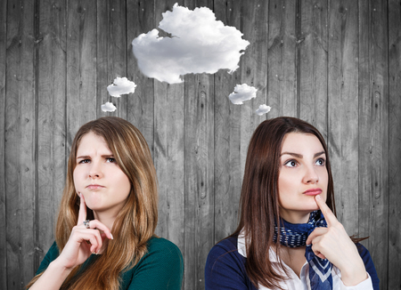 daydream: Young women daydream with white cloud owerhead on the gray wooden wall background