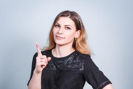 threaten: Young beautiful woman threaten finger on gray background