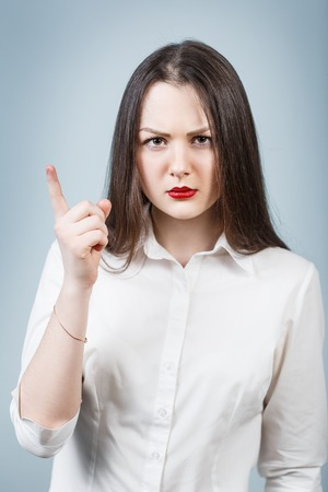 threaten: Young angry woman threaten finger on the gray background Stock Photo