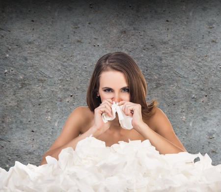 hanky: Ill woman with a lot of hankys on the gray wall background Stock Photo