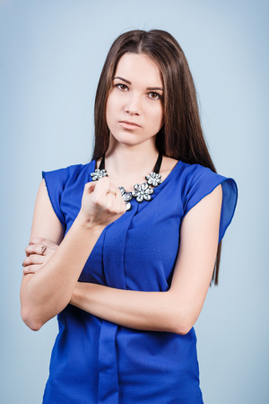strict: Strict beautiful woman shows threaten fist on the blue background