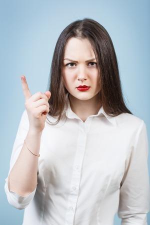 Mujer enojada joven amenazan el dedo en el fondo azul