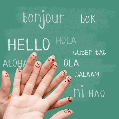 guten tag: Hello in various languages on a green chalkboard Stock Photo