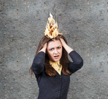 Young woman with a headache and burning fire Stock Photo