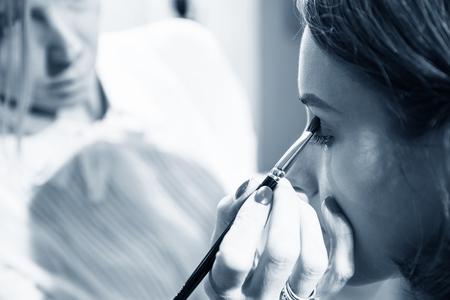 estilista: Mujer joven estilista hace maquillaje hermosa ni�a en el sal�n