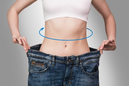 Young girl shows her weight loss by wearing jeans on the gray background