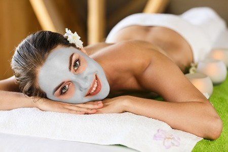 massagist: Young beautiful woman with cly mask lying on massage table and enjoying massage. Spa concept,