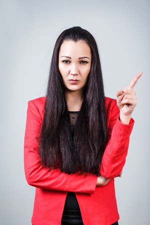 threaten: Young beautiful woman threaten finger on the gray background