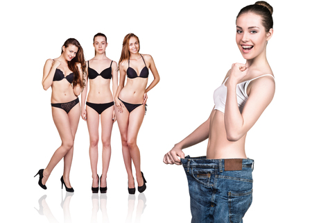 accomplishing: Woman became skinny and wearing old big jeans Stock Photo