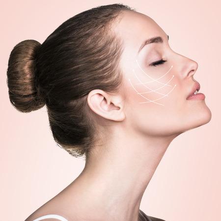 Close-up Porträt der jungen, schöne und gesunde Frau mit Pfeilen auf ihrem Gesicht. Spa, Chirurgie, Gesichtslifting und Make-up-Konzept