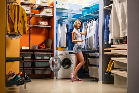 La muchacha hermosa está sonriendo y elección de la ropa del marido en un vestuario