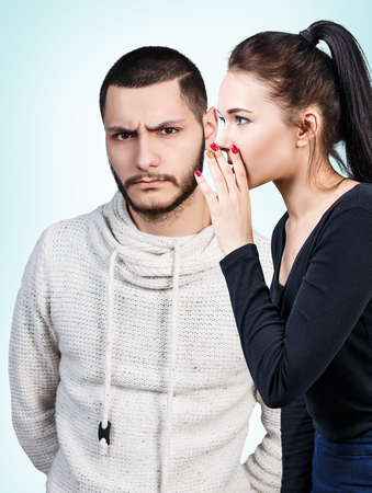 displeased: Young girl whispering some secret to young displeased man over blue background