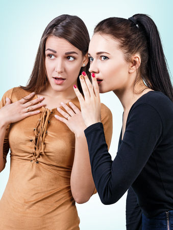 blab: Young girls gossiping some secret over blue background Stock Photo