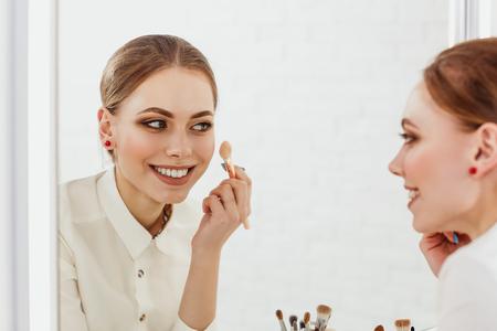 cheekbones: Beauty woman applying makeup. Beautiful girl looking in the mirror and applying cosmetic on the cheekbones.