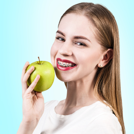 overbite: Young woman with teeth braces holds green apple on the blue background