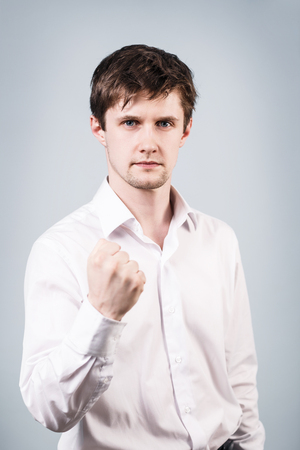 threaten: Young handsome businessman shows threaten fist on the gray background