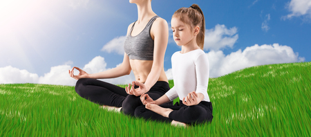 position d amour: Young woman and her daughter doing yoga exercise outdoors
