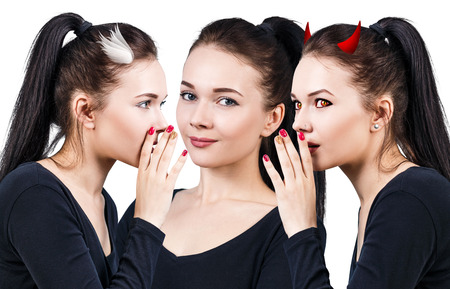 hesitating: Beautiful young woman with angel and demon whispering isolated over white background Stock Photo