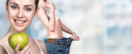 oversize: Young slim woman holding an apple and wearing oversize jeans over blurred background