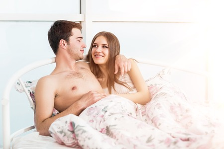 blight: Portrait of beautiful couple laying on bed in room with blight sunlight