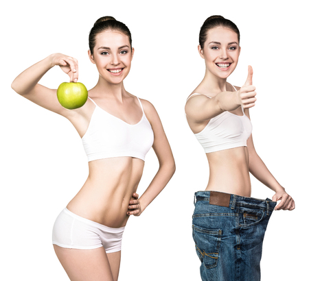 oversize: Young woman with apple showing weight loss result by wearing oversize jeans