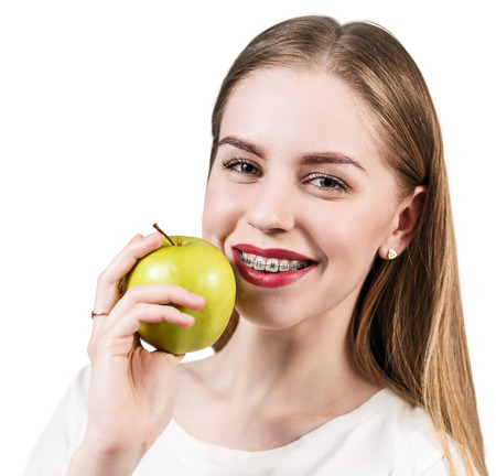 overbite: Beautiful young woman with brackets on teeth eating apple isolated on white