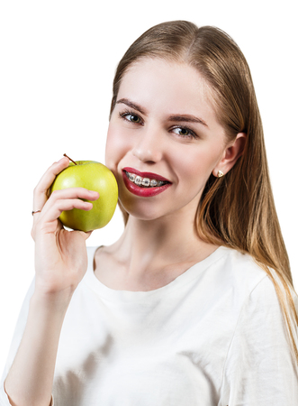 crooked teeth: Beautiful young woman with brackets on teeth eating apple isolated on white