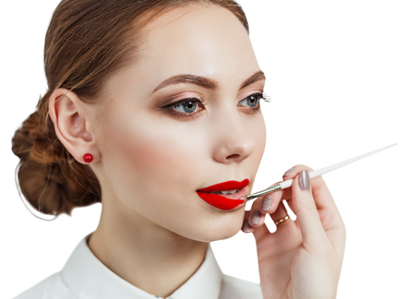applying lipstick: Young woman applying lipstick with an applicator isolated on white