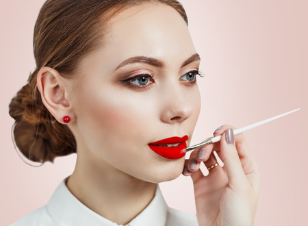 applying lipstick: Young woman applying lipstick with an applicator over pink background