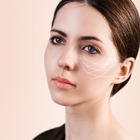 antiaging: Young female face with clean fresh skin over biege background. Antiaging concept