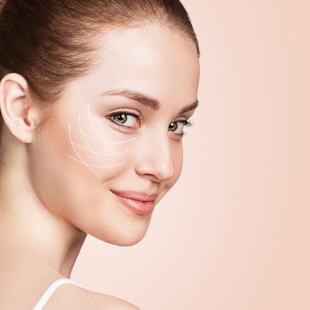 biege: Young female face with clean fresh skin over biege background. Antiaging concept