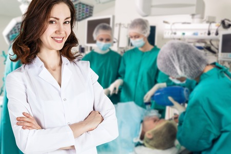 white robe: Young doctor woman in white robe stands on the surgeon team background