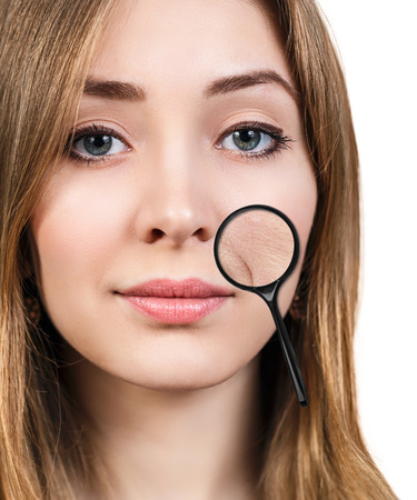 aging skin: Young woman with magnifying glass showing aging skin isolated on white