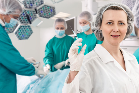 anesthetist: Adult female anesthetist with syringe on the surgery teem background Stock Photo