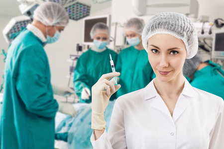 anesthetist: Young female anesthetist with syringe on the surgery teem background