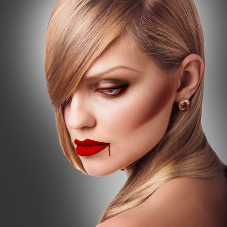 Portrait of young vampire sexy woman with red lipstick over gray background Stock Photo