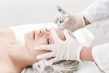 revitalization: Young pretty woman receiving treatments in beauty salons. Contouring procedure , revitalization. Beauty injections .