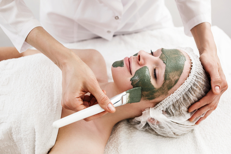 renew.: Attractive young woman with clay mask on face in spa salon.