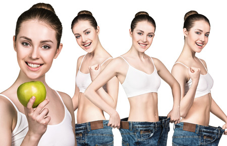 oversize: Young slim woman holding an apple and wearing oversize jeans over white background