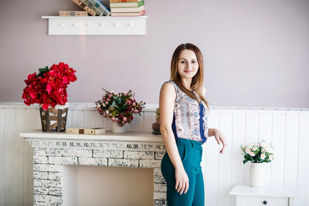 leaned: Young woman posing leaned on the sham fireplace in the room Stock Photo